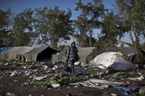 A refugee walking in front of small tents and garbage